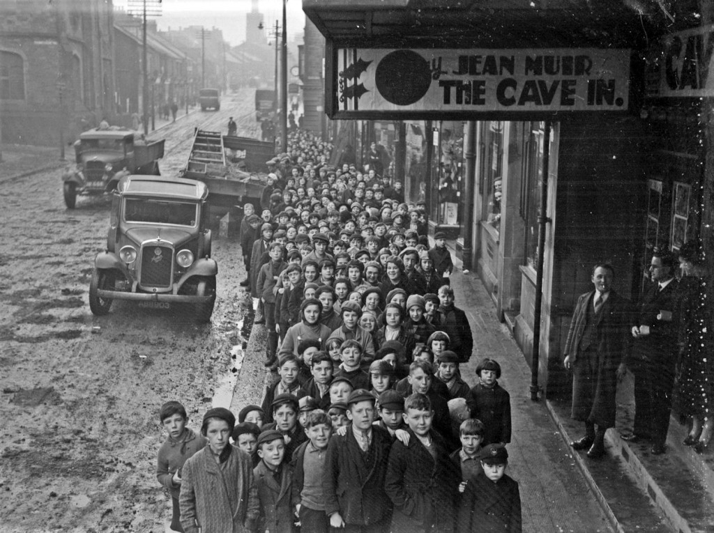 "Long queue of children outside the Essoldo Cinema, Stanley waiting to see ""The Cave In"" starring Jean Muir. Note muddy un-tarmaced road. 30th or 31st December 1937. Photo no. 67128"